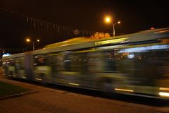 A blurred bus in the street in the evening. The motion of a blurred bus in the street in the evening royalty free stock photography