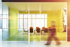 Bright yellow office conference room, businessman. Blurred businessman walking in a bright yellow boardroom with panoramic windows and a king size table Stock Images