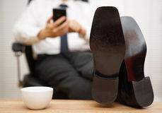 Blurred businessman  is working on smart mobile phone, focus on Royalty Free Stock Photos