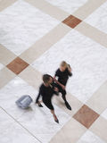 Blurred Businesswomen Walking With Suitcase On Tiled Floor Stock Photography