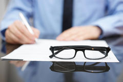 Blurred busy entrepreneur in background with focus on glasses Stock Photos