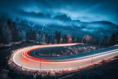 Blurred car headlights on winding road in mountains. With low clouds at night in autumn. Moody landscape with asphalt road, light trails, foggy forest, rocks royalty free stock photos