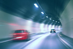 Blurred car high speed tunnel driving. Tunnel dangerous high speed motion blurred vehicle driving. Blue color filter used. Motion blur visualizies the speed and Stock Photos