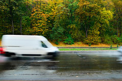Blurred car in motion on wet road Stock Images