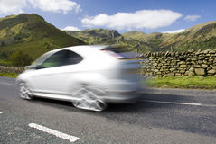 Blurred car on the mountain road, UK. Blurred car on the mountain road, Lake District National Park, Cumbria, UK Royalty Free Stock Photo