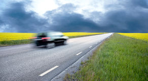 Blurred car in rape field Royalty Free Stock Photo