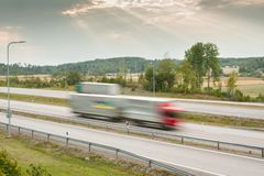 Blurred cars in motion. Asphalt road with cars at autumn beautiful sunset in Finland stock photography