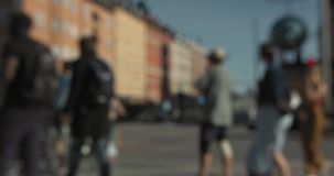 Blurred cars and people walking and bicycling at an intersection in central Stockholm. stock video footage