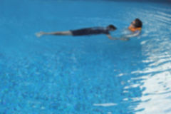 Blurred children playing in the pool Royalty Free Stock Image