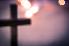 Blurred Christian Cross and Bokeh Lights. A background of bokeh lights with a soft, out of focus, wooden cross royalty free stock photo