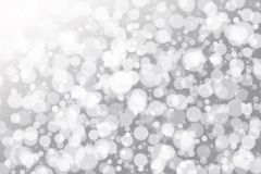 Blurred christmas holidays lights bokeh. Gray abstract hide background with white sparks and stars and light Stock Image