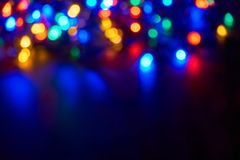 Blurred christmas lights on dark background. Blurred bokeh christmas lights in blue, red, yellow, orange and green on dark background Stock Photo