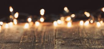 Blurred christmas lights on wooden rustic table. Moody christmas background Stock Image