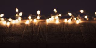 Blurred christmas lights on wooden rustic table. Moody christmas background Stock Photography