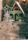 Blurred christmas . Silver toy Christmas tree with a star in front and blurred Christmas house away. Background for a vintage post. Card. Toned image Stock Image
