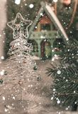 Silver toy Christmas tree with a star in front and blurred Christmas house away. Drawn snow. Background for a Royalty Free Stock Images