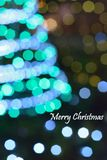 Blurred christmas tree lights with merry christmas text Stock Images