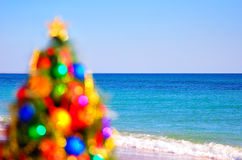 Blurred christmas tree on the sand in the beach Royalty Free Stock Photo