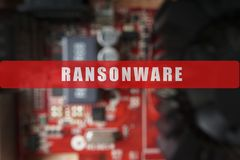 Blurred of a circuit board with big microchip . Cyber security concept with ransonware text.  Stock Photos