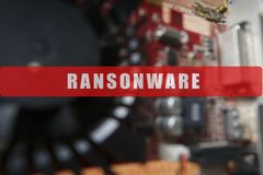 Blurred of a circuit board with big microchip . Cyber security concept with ransonware text.  Stock Image