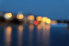 Blurred city lights with bokeh effect reflected on water surface. Stock Image