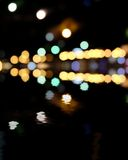 Blurred city at night, bokeh background. Yellow and green spots on black Stock Photography