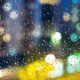 Blurred city night illumination through rain drops stock image