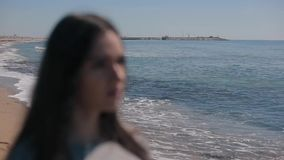 A blurred close view of a girl on the seashore. The woman putting on sunglasses and getting pure vision. A blurred portrait of a young girl standing on the beach stock video