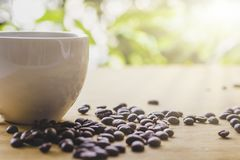 Blurred coffee beans are placed around a cup of coffee on the table royalty free stock photos