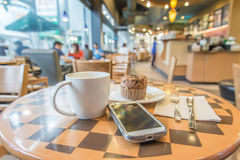 Blurred coffee shop,Vintage filter. A cup of coffee ,mupfin cake and smart phone on the wood table Stock Photos