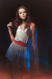 Blurred color art portrait of a girl on a dark background. Fashion woman with beautiful makeup and a light summer dress. Sensual Stock Photos