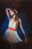 Blurred color art portrait of a girl on a dark background. Fashion woman with beautiful makeup and a light summer dress. Sensual Stock Photo