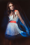 Blurred color art portrait of a girl on a dark background. Fashion woman with beautiful makeup and a light summer dress. Sensual royalty free stock photography