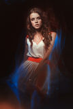 Blurred color art portrait of a girl on a dark background. Fashion woman with beautiful makeup and a light summer dress. Sensual Stock Image
