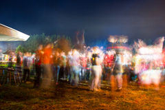 Blurred colored silhouettes of dancing people. Night Royalty Free Stock Image