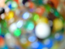 Blurred Colorful Bokeh, Glass Marbles and Beads. Saw this toy box full of vibrantly colored glass beads and marbles, shot it in the sunlight Stock Photos