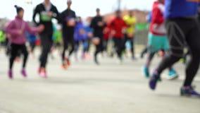 Blurred colorful crowd of people running at city marathon on asphalt road