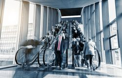 Blurred business people rushing at a escalator. Blurred commuters rushing on escaltors in a  trade show. ideal for websites and magazines layouts Stock Image