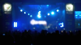 Blurred Concert Crowd at Music Festival. Crowd people dancing Rock concert. Weighed, applauds, raises his hands up and photographed, filmed concert on the stock footage