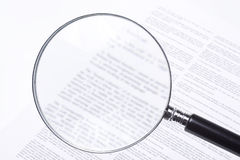 Blurred and confusing fine print. Legal mumbo jumbo is confusing, even with a magnifying glass on the fine print. Isolated in a studio setting, on white stock photo