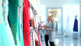 Blurred consultant and buyer on the background selection the dress in women`s clothing store. stock video