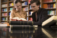 Blurred Couple At Library Desk With Focus On Books. Blurred young men and women studying at desk in library with focus on books in foreground Royalty Free Stock Images