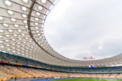 Blurred crowded football stadium with stands and spectators. 2016 sport background. Blurred crowded football stadium with field, stands and spectators. 2016 Stock Photo