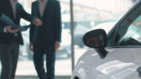 Blurred customer and seller behind a car stock video footage