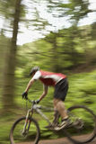 Blurred Cyclist On Countryside Track. Side view of a blurred male cyclist on countryside track Royalty Free Stock Photo