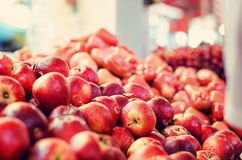 Fresh raw red apples fruit on market stall in Malaysia. Blurred and defocus shot image of fresh raw red apples fruit on market stall in Malaysia Royalty Free Stock Image
