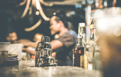 Blurred defocused side view of barman at cocktail bar. Blurred defocused side view of barman and people drinking and having fun at cocktail bar - Social stock image