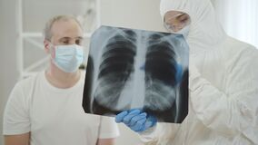 Blurred doctor in antiviral suit talking to mid-adult man in face mask showing Covid-19 complications on lungs roentgen