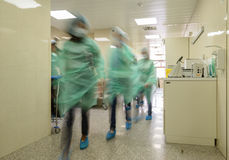 Blurred doctor figures wearing medical uniforms in hospital corr Stock Photography