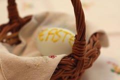 Blurred Easer egg inside basket. Easter egg with painted Easter letters inside basket. Focus on basket handle Stock Photos